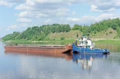 Volga, Rússia - 2 de junho 2016 Um reboque do rio empurra uma barca ao longo do rio de Volka perto de um banco verde coberto com  Fotografia de Stock Royalty Free