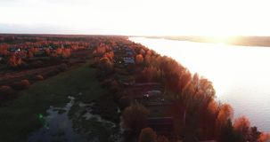 Volga river in autumn at sunrise aerial view from flying quadcopter over forest. stock video footage
