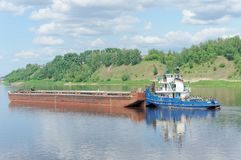 Volga, Russia. - June 2.2016. A river tug pushes a barge along the Volka River near a green bank covered with grass and bushes Royalty Free Stock Photography