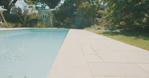 Volgend schot van een zwembad in een grote binnenplaats stock videobeelden