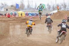 Volgograd, Rússia - 19 de abril de 2015: Alguns cavaleiros em busca do líder, na fase da cruz aberta da motocicleta do campeonato Fotografia de Stock Royalty Free