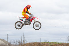 Volgograd, Rússia - 19 de abril de 2015: Piloto da motocicleta que salta no trampolim em voo, na fase do campeonato aberto Mo Fotos de Stock Royalty Free
