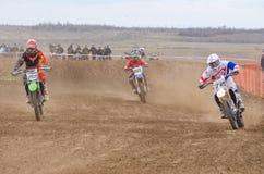 Volgograd, Rússia - 19 de abril de 2015: Três cavaleiros na trilha, na fase do copo aberto do corta-mato da motocicleta do campeo Fotos de Stock