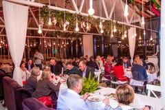 Volgograd, Rússia - em fevereiro de 2019: Muitos povos jantam no restaurante Luz brilhante imagens de stock