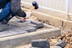 The worker stacks stone blocks on the road. VOLGOGRAD, RUSSIA - April 23, 2018: The worker stacks stone blocks on the road Royalty Free Stock Photography