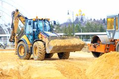 The yellow tractor in work earthwork. VOLGOGRAD, RUSSIA - April 23, 2018: The yellow tractor in work earthwork with sand, at construction of the Arena stadium Royalty Free Stock Images