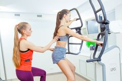 VOLGOGRAD, RUSSIA - DECEMBER 7, 2017: Training with a personal trainer in the fitness club v club on the simulator of royalty free stock photos