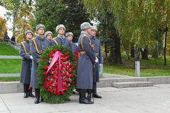 Soldiers keep a wreath on a grave in an overcoat. VOLGOGRAD, RUSSIA - October 15, 2017: Soldiers in a gray overcoat hold a wreath on a grave in hand on the Royalty Free Stock Photography