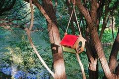 Volière avec un toit rouge accrochant sur un arbre près de la rivière photo libre de droits