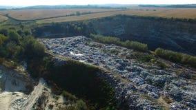 Voli intorno allo scarico di rifiuti vicino ai campi agricoli del weat Siluetta dell'uomo Cowering di affari archivi video