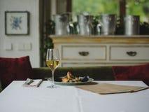 Volkomen gediend voedsel bij een vage restaurantachtergrond Installatie van gekookte zeevruchten en een glas champagne De ruimte  stock foto