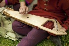 Volks musicus met gusli stock afbeeldingen