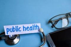 Volksgezondheidsinschrijving met de mening van stethoscoop, oogglazen en smartphone op de blauwe achtergrond royalty-vrije stock foto's