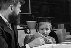 Volksschulbildungskonzept Kind studiert mit dem Lehrer und hört mit Aufmerksamkeit Lehrer und Schüler in der Doktorhut stockfotos
