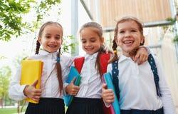 Volksschule des gl?cklichen Kinderfreundinschulm?dchenstudenten lizenzfreie stockbilder