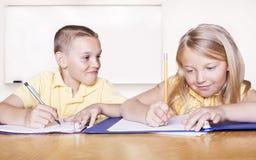 Volksschule-Kursteilnehmer, die Heimarbeit tun Lizenzfreie Stockfotografie