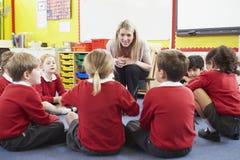 Volksschule-Schüler, die dem Lehrer Geschichte erzählen Stockbild