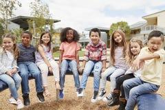 Volksschule scherzt das Sitzen auf Karussell im Schulhof lizenzfreie stockbilder