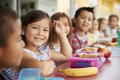 Volksschule scherzt das Sitzen einer Tabelle mit Lunchpaketen lizenzfreies stockfoto