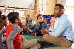 Volksschulekinder und -lehrer sitzen queresmit beinen versehenes auf Boden Lizenzfreie Stockfotografie
