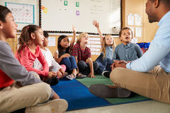 Volksschulekinder und -lehrer sitzen queresmit beinen versehenes auf Boden Lizenzfreie Stockfotos