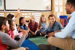 Volksschulekinder und -lehrer sitzen queresmit beinen versehenes auf Boden Lizenzfreies Stockfoto