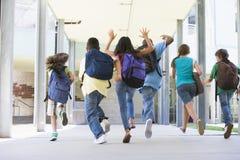 Volksschulepupillen, die draußen laufen Lizenzfreie Stockfotos
