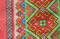 Volkstextilverzierung von hellen Farben, aus Mustern von geometrischen Formen und von Linien bestehend stockbild