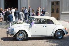 Volkswagen Beetle fuera de la iglesia después de la ceremonia de boda Imagen de archivo