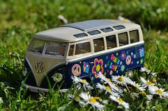 Volkswagen Beige and Blue Van Scale Model Near White Daisy Flower during Daytime Stock Image