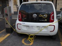 Volkswagen e-Up plug-in hybrid electric car stands by charging station, in Genoa, Italy. stock images