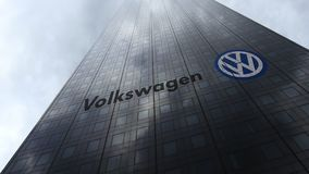 Volkswagen-embleem op een wolkenkrabbervoorgevel die op wolken wijzen Het redactie 3D teruggeven Royalty-vrije Stock Foto's