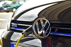 Volkswagen Golf GTE wordt geladen bij een het laden post stock foto's
