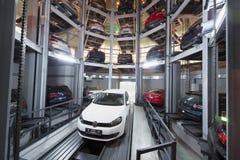 Volkswagen Golf på elevator i lokal för lagringsbilar Arkivfoto