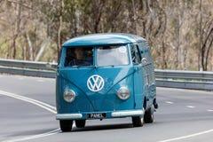 Volkswagen Kombi skåpbil som 1959 kör på landsvägen arkivfoto
