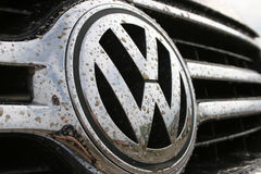 Volkswagen logo in dirt. Car brand Volkswagen logo covered in muddy water and dirt, ideal for coverage of VW's recently announced rally activities. Car in image Royalty Free Stock Images