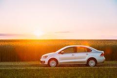 Volkswagen Polo Car Parking On Wheat fält Dramatisk solnedgångsoluppgång Fotografering för Bildbyråer