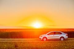 Volkswagen Polo Car Parking On Wheat fält Solnedgångsoluppgångdrama Royaltyfria Bilder