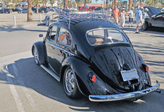 1960 Volkswagon. This black 1960 Volkswagon has a roof rack, after market wheels, and a high performance exhaust system. In 1966, you could by a brand new VW for Royalty Free Stock Photo