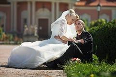 Voll vom stilvollen Bräutigam der Liebe mit blonder Braut auf dem Hintergrund Stockbilder