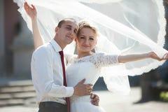 Voll vom stilvollen Bräutigam der Liebe mit blonder Braut auf dem Hintergrund Stockfotografie