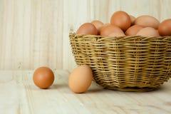 Voll von den Eiern setzen Sie sich in einen Weidenkorb im hölzernen Hintergrund Lizenzfreie Stockfotos