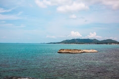 Voll von den Felsen auf der Küste und idyllischen blauen dem Meer- und klarenhimmel T Stockfoto
