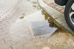 Voll Wasser auf der Straße wegen der verstopften Ableitung Lizenzfreies Stockfoto