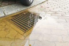 Voll Wasser auf der Straße wegen der verstopften Ableitung Stockfotografie
