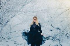 Volle Frau in einem dunklen Kleid, das im Wald in Winter tanzt lizenzfreie stockbilder