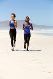 Volle gesunde Frauen des Körpers zwei, die auf dem Strand laufen Stockfotos