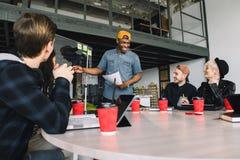 Volle Konzentration bei der Arbeit Unternehmensteamarbeitskollegen, die im modernen B?ro arbeiten Afrikanischer Mann, der Darstel lizenzfreies stockbild