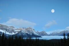 Volle maan die over Canadese Rockies wordt geplaatst Stock Foto