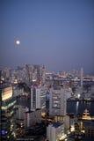 Volle maan en verlichte gebouwen in Tokyo stock afbeelding